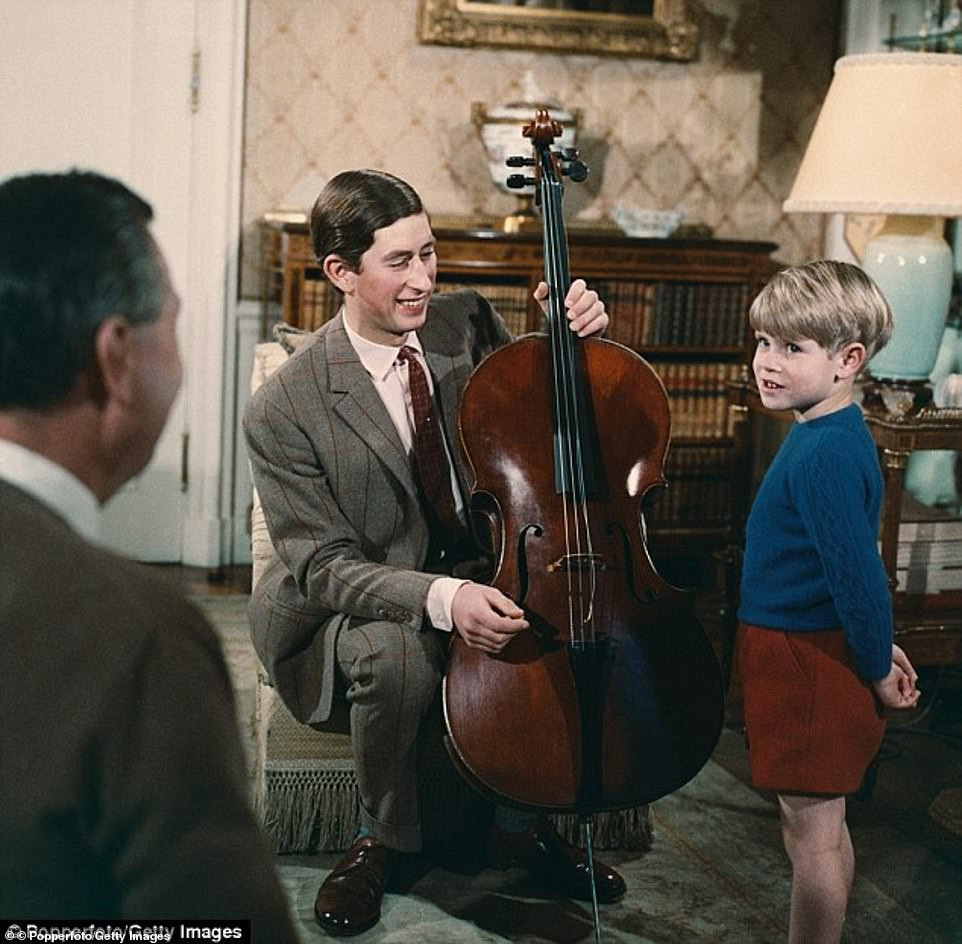 Prince Charles, holding a cello instrument, pictured together with his younger brother Prince Edward (right) during filming of the television documentary 'Royal Family' in London in 1969