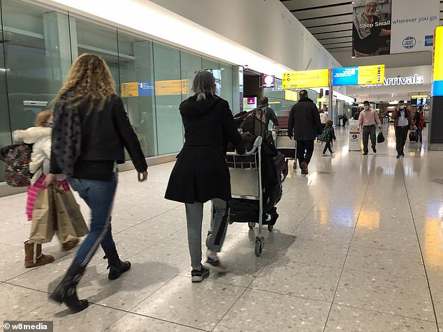 Air passengers walk into the arrivals hall at London Heathrow Airport this morning as flights continue to come into the UK