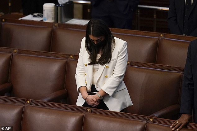 Congresswoman Alexandria Ocasio-Cortez said she feared for her life during the riots on the Capitol building on Wednesday. Pictured: AOC bows her head during a closing prayer of a joint session of the House and Senate to confirm Electoral College votes at the Capitol, early Thursday