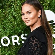 Chrissy Teigen Mimics Cher's 90s Fitness Video In Sexy Sheer Bodysuit & Curly Wig — Watch