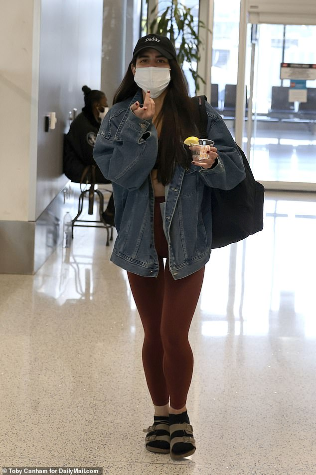 Defiant SoHo Karen Miya Ponsetto arrives back in LA (with a drink in hand) after arraignment in NY