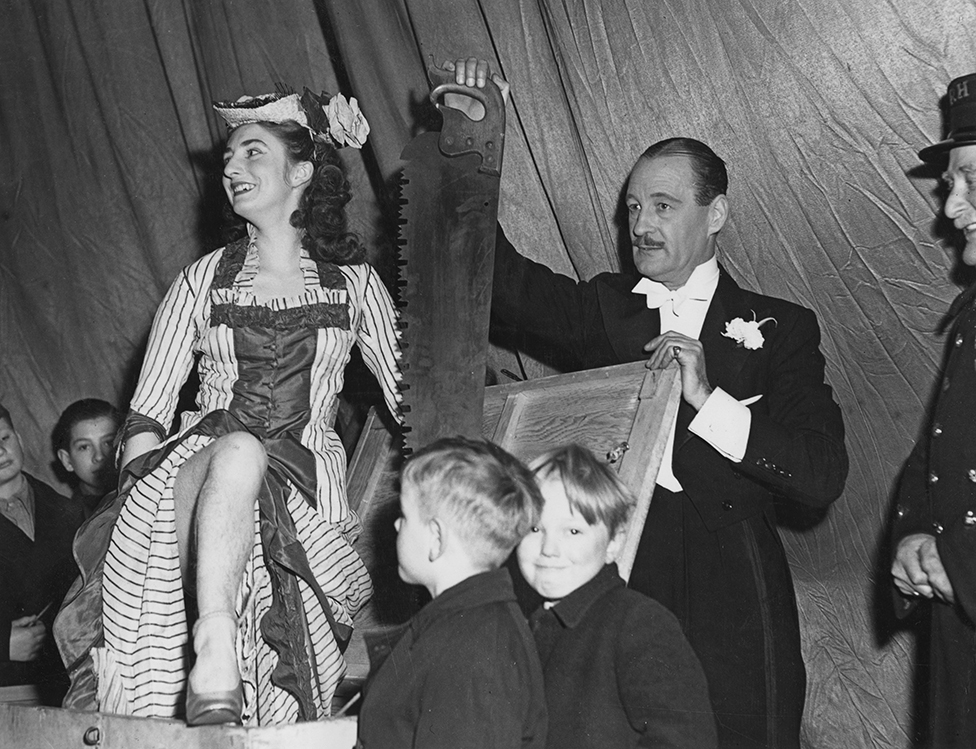 British magician Jasper Maskelye prepares to saw his assistant, Maisie Wright, in London in 1948