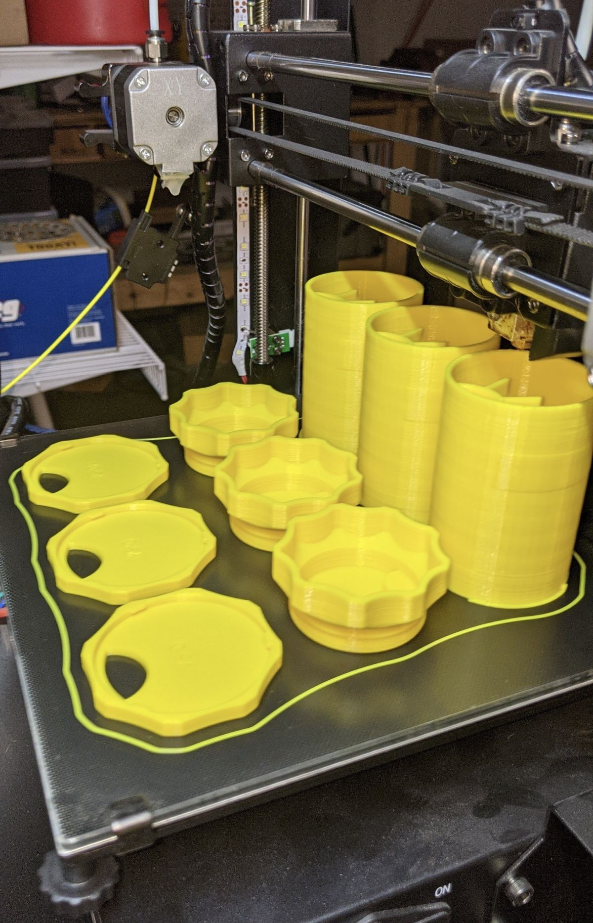 Three yellow bottle bodies, three caps, and three bases sitting on a 3D printer.