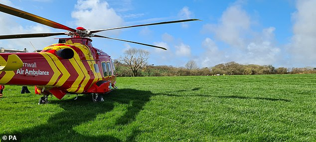 ACornwall Air Ambulance helicopter in a field adjacent to the crash site