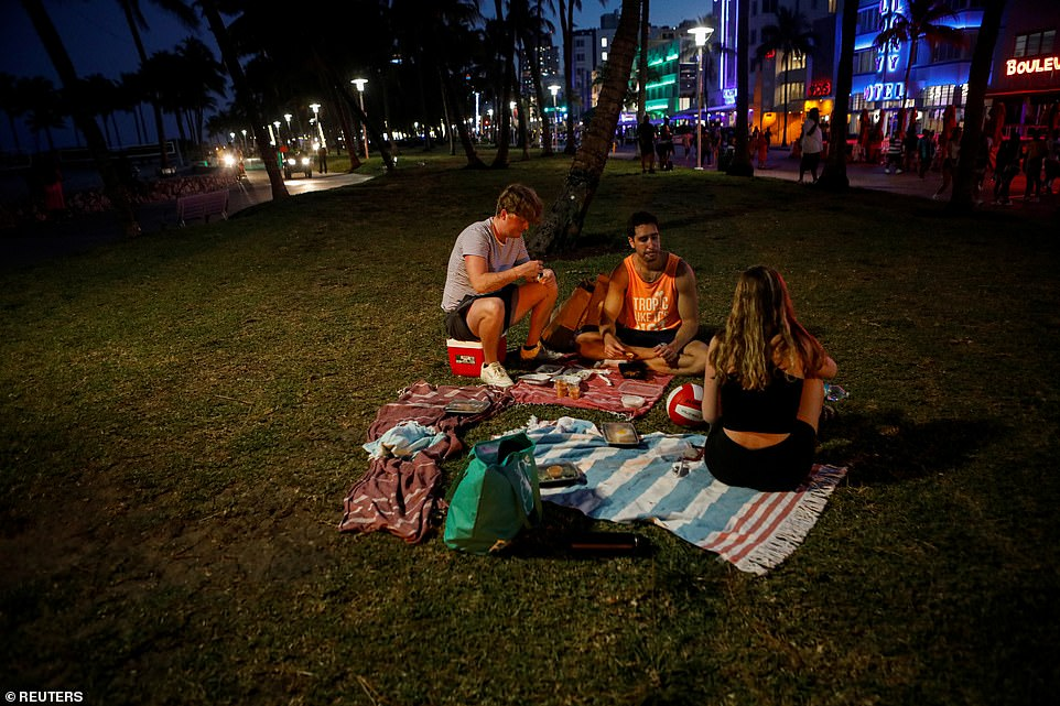A group of spring breakers sit for a picnic on Ocean Beach