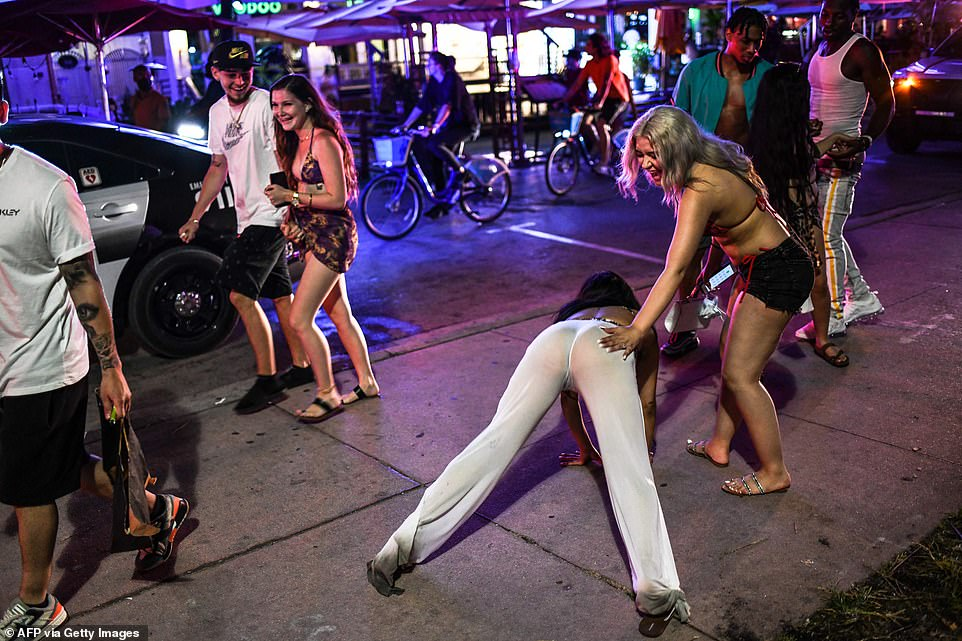 People dance as Miami Beach Police escort them out of Ocean Drive as curfew is in effect in Miami Beach on March 25