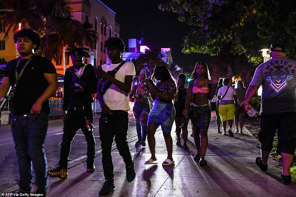 Miami Beach Police escort people off Ocean Drive as curfew is in effect in Miami Beach, Florida, on March 25
