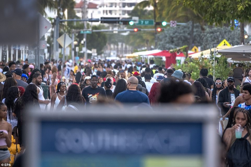 People attend a party on a walkway near the beach, during spring break in Miami Beach on March 25
