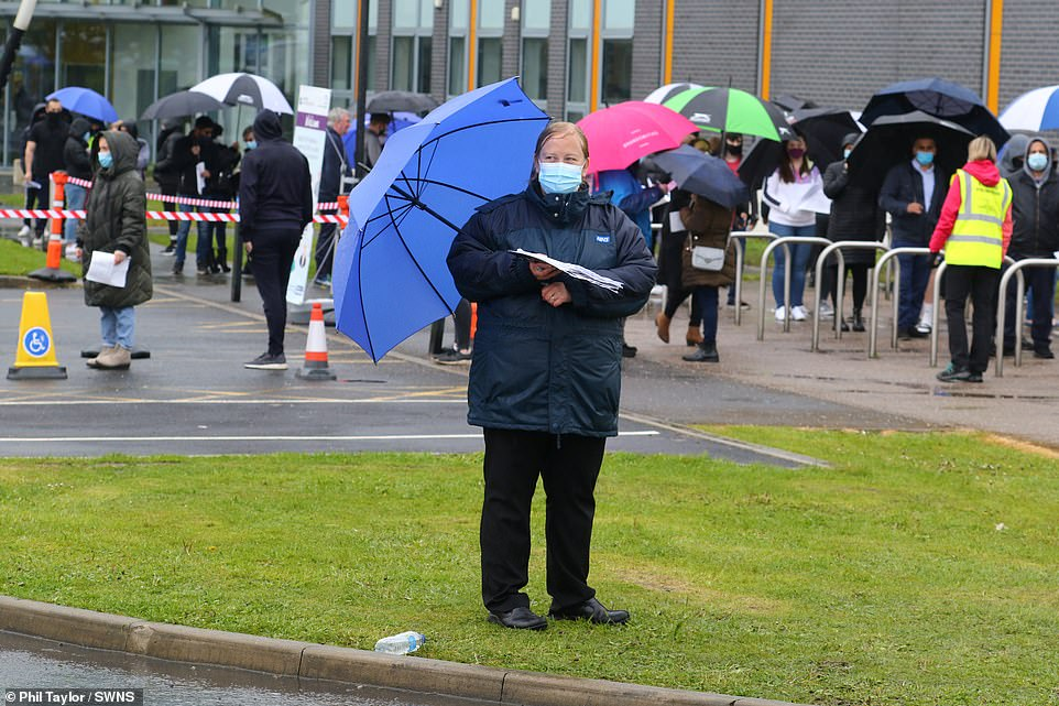 A NHS worker stands outside as members of the public living in Bolton arrive to receive their coronavirus vaccine this afternoon