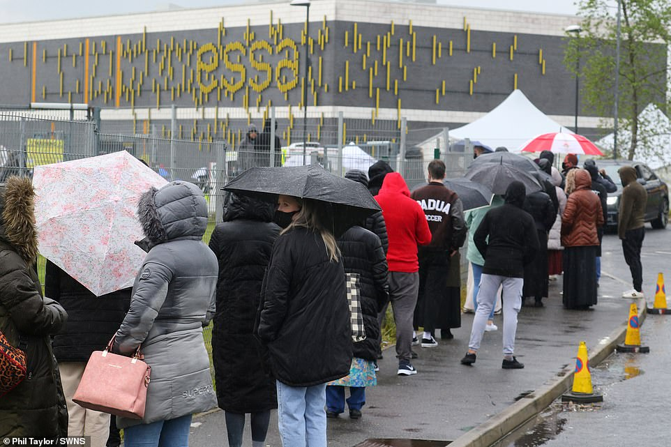 Hundreds of people queue on the streets of Bolton this afternoon as part of efforts to speed up Britain's vaccine race