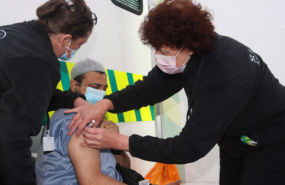 A man receives his Covid vaccination at a pop up centre at the Essa Academy school in Bolton earlier this afternoon