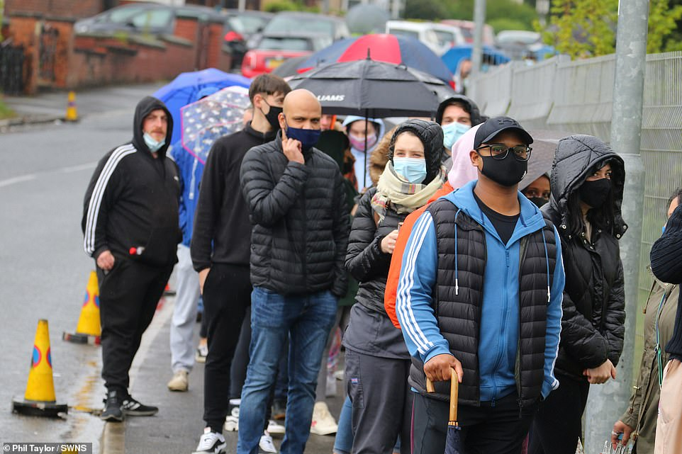 People wear face masks and carry umbrellas as they wait to have their coronavirus injections in Bolton today