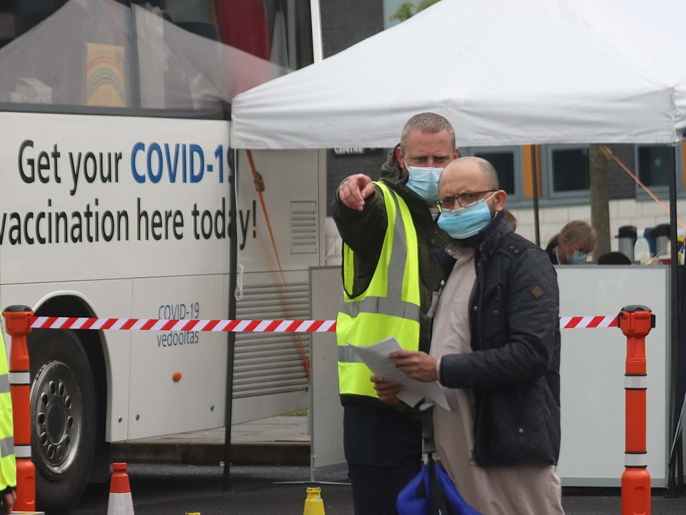 A worker directs a patient to a Covid vaccination centre in Bolton. The area is also undergoing surge testing