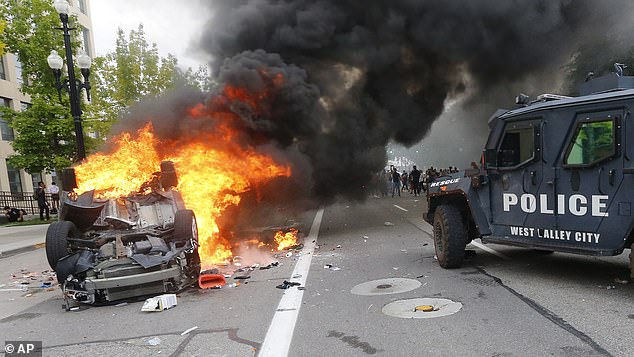 A police vehicle drives past a burning car on May 30, 2020, in Salt Lake City during a protest after Floyd was killed