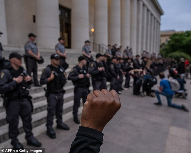 Protesters kneel and raise their arms if front of a row of police officers as they gather peacefully to protest the death of George Floyd at the State Capital building in downtown Columbus, Ohio, on June 1, 2020