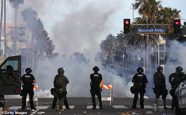 Police watch as tear gas is deployed during demonstrations in the aftermath of George Floyd's death on May 31, 2020 in Santa Monica, California.