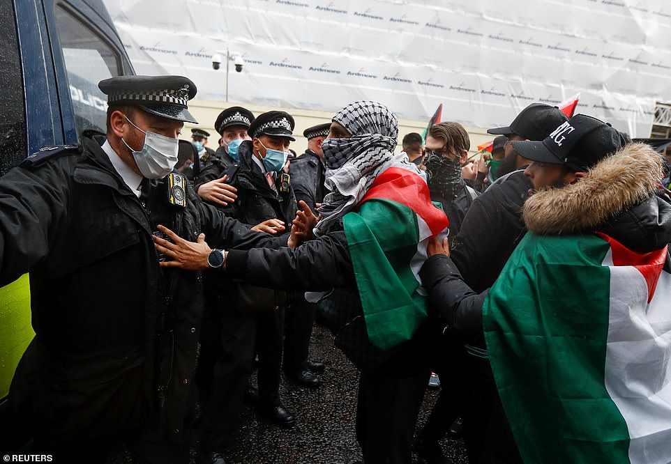 Pro-Palestinian demonstrators scuffle with police during a demonstration in London on Sunday