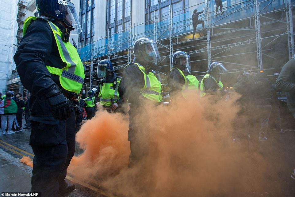 Free Palestine protesters throw drinks, eggs and flares at the police in Kensington, central London near the Israeli Embassy.Police were injured on Saturday in clashes with pro-Palestine protesters in London, as thousands marched through London's Hyde Park to the Israeli Embassy in solidarity with the people caught in ongoing conflict with Israel